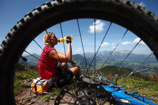 KITZBUHEL, AUSTRIA - AUGUST 16:  A female mountainbiker on the Hahnenkamm drinking a mineraldrink with a view on the Kaisergebirge on August 16, 2009 in Kitzbuhel, Austria. Kitzbuehel is famous for its Hahnenkamm alpine skiing downhill skirace and a lot of VIPs.  (Photo by EyesWideOpen/Getty Images)