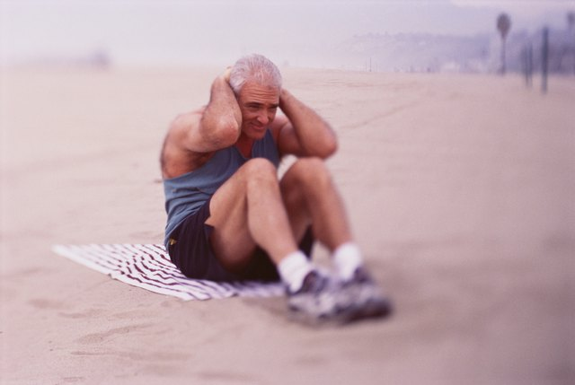 Man doing sit-ups on the beach