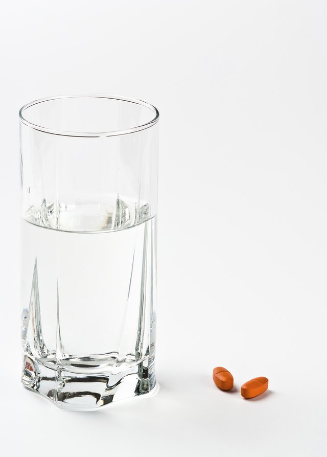 two pills and glass of water