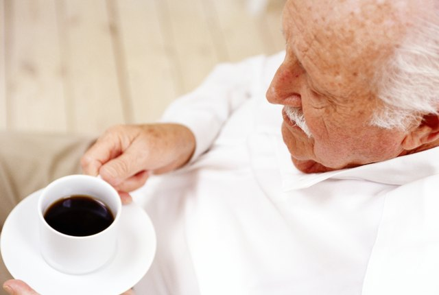 high angle view of an elderly man holding a cup of black coffee