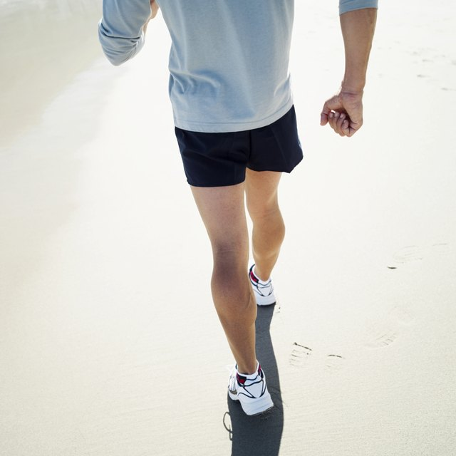 Close-up of the legs of a man walking on the beach