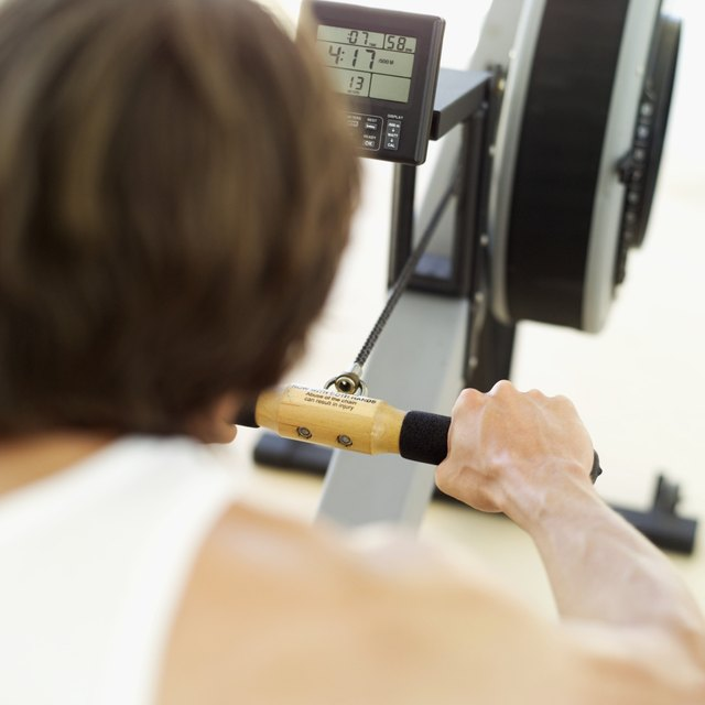 Rear view of a young man exercising on a rowing machine