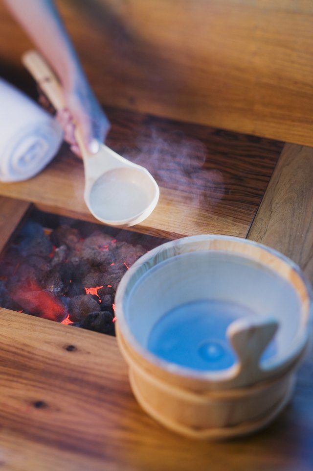 Person pouring water onto hot rocks in sauna