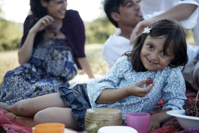 girl eating grape, family behind
