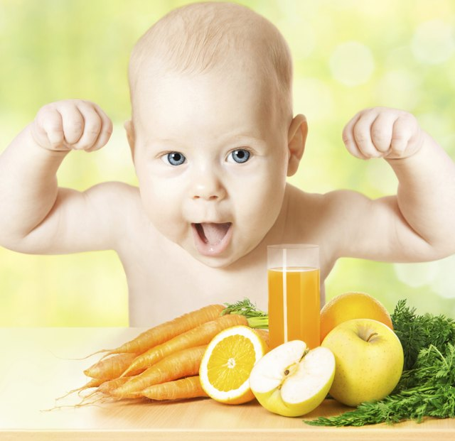 Sprong baby with raised hands, fresh fruits, vegetables, juice glass
