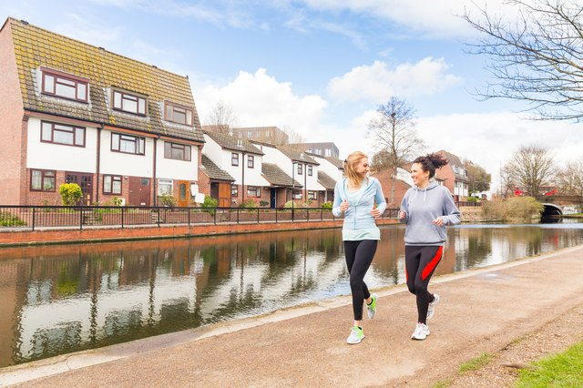 Two girls jogging outdoors in London. They are caucasian women, looking each other while running along a canal with some beautiful houses on background on a sunny day in spring.