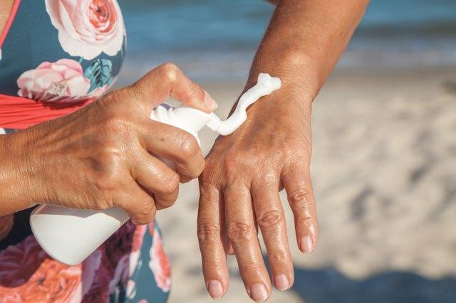 Elderly woman in swimsuit using cream for hand on beach