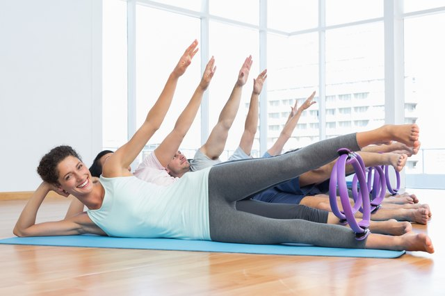 Class stretching legs and hands in row at yoga class