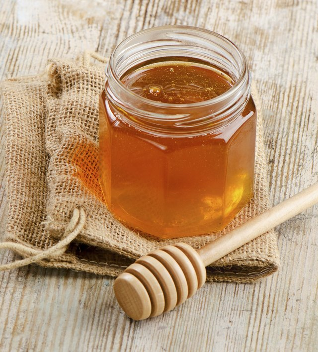 Jar of honey with wooden stick