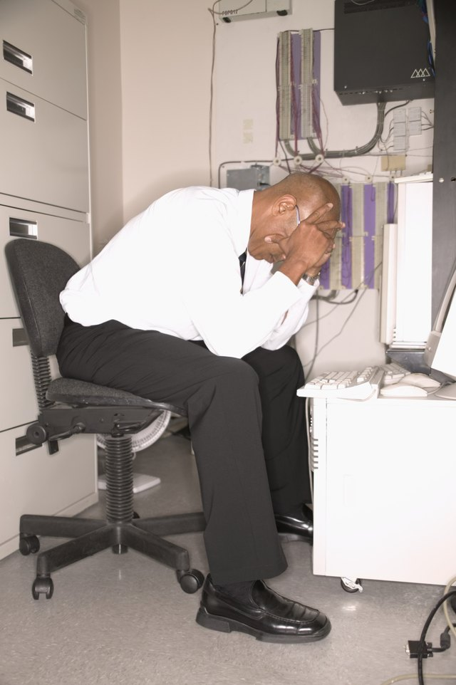Businessman sitting at a desk resting his head on his hands