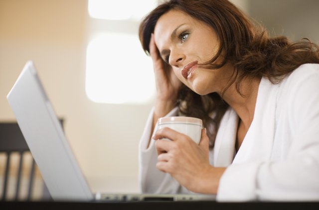 Distraught woman working at home with laptop computer