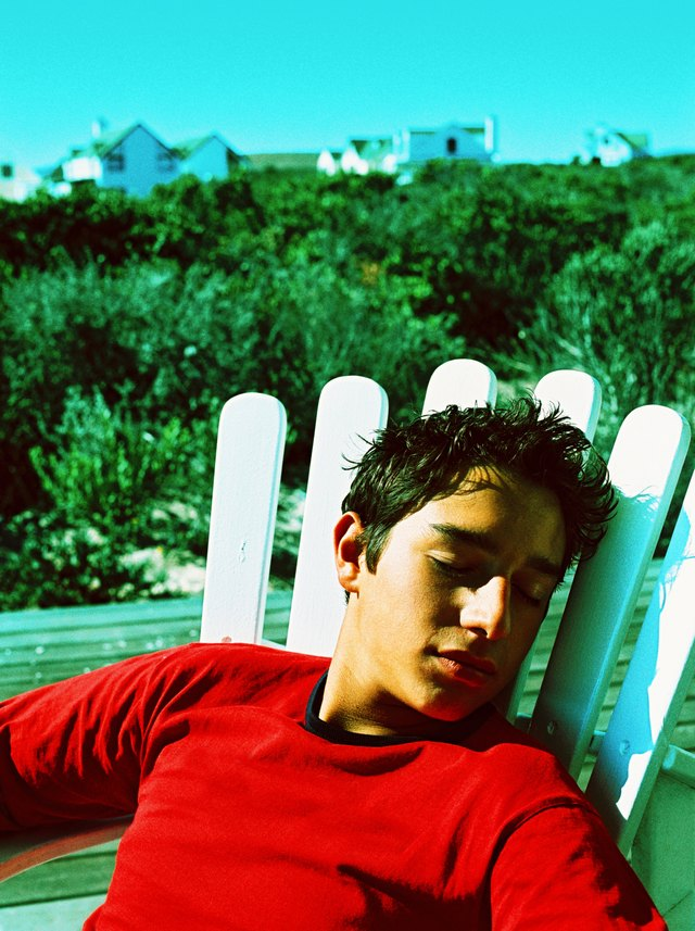 a young teenage boy sleeping on a chair