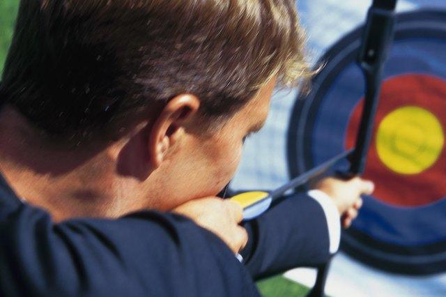 Man aiming bow and arrow at target