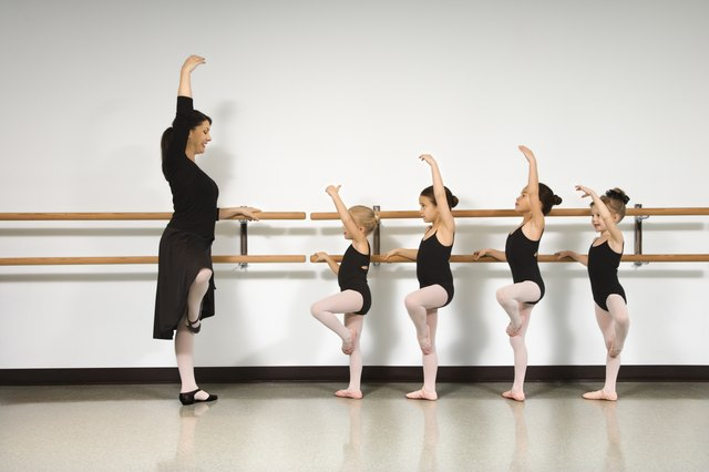 Ballet instructor demonstrating for students standing at the barre