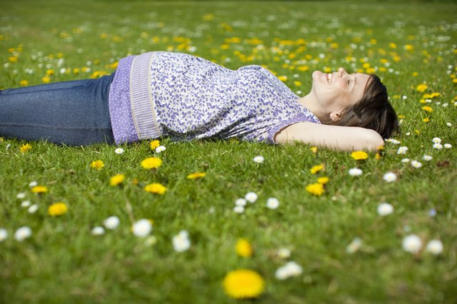 Pregnant woman lying on grass