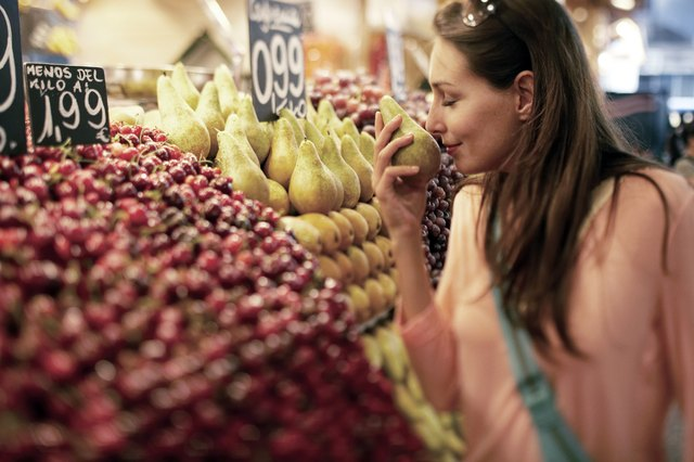 Woman Smelling at Pear at Fruit Stand