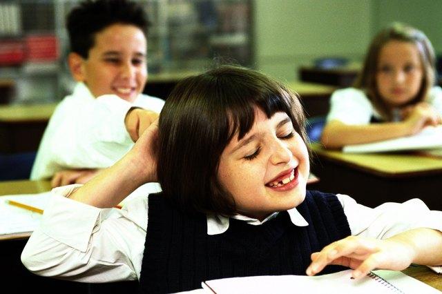 portrait of a school boy (8-10) pulling a girls hair in class