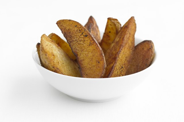 Potato wedges in a white bowl, studio shot