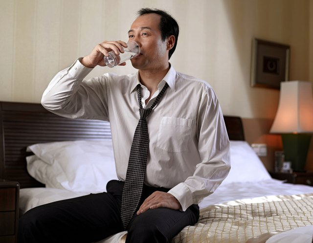 Businessman drinking water while sitting on bed.