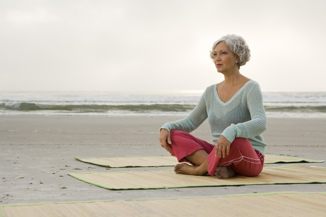 Mature woman exercising on a mat at the beach