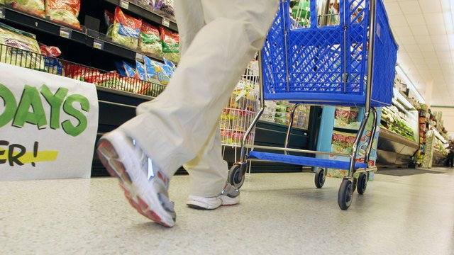 Low section view of a person walking with a shopping cart in a supermarket