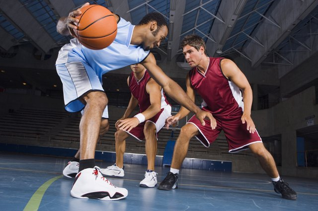 Man dribbling basketball against defenders