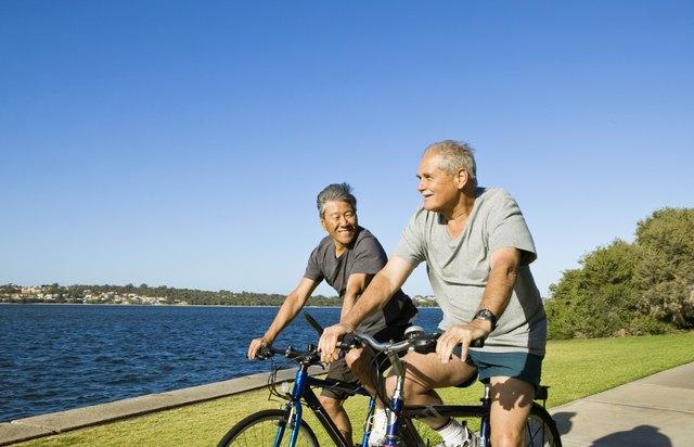Men riding bikes by lake