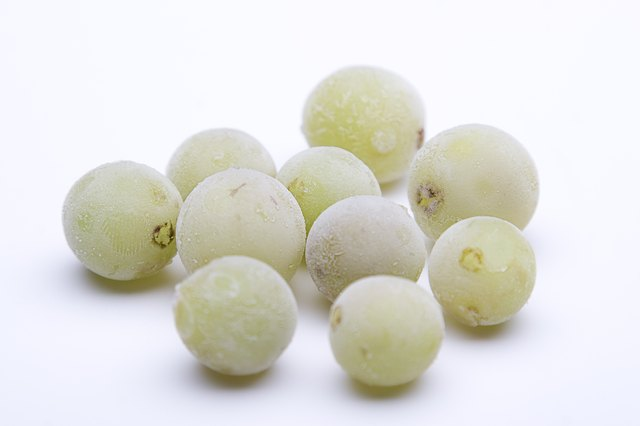 Frozen green grapes against white background