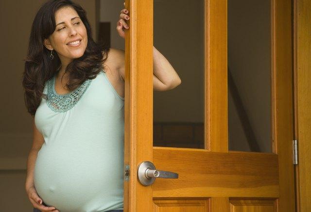 Pregnant Hispanic woman in doorway smiling
