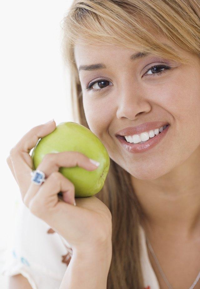 Hispanic woman eating apple