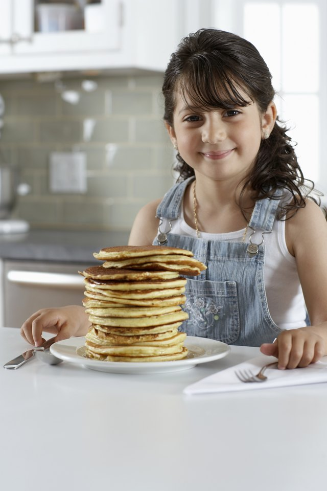 Girl (4-6) sitting at plate of pancakes, smiling, portrait