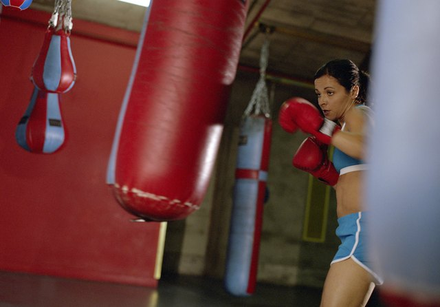 Young female boxer punching heavy bag