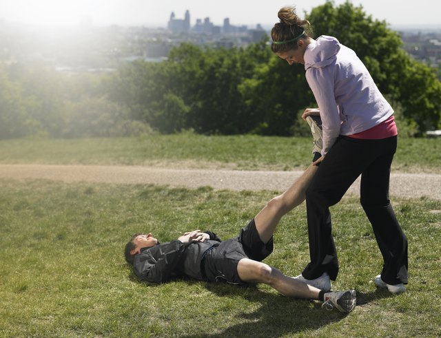 Mid adult man lying on grass after exercising, woman standing doing massage, city in background