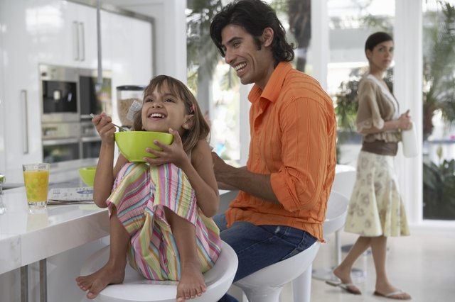 Father sitting with daughter (7-9) having breakfast in kitchen