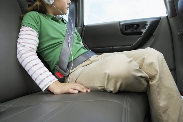Girl (6-8 years) sitting on rear seat of car, close-up, side view