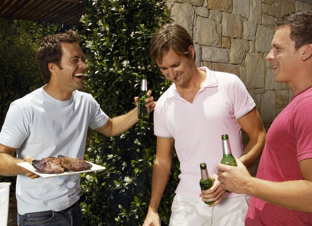 Three young men holding beer bottles and plate of meat, laughing