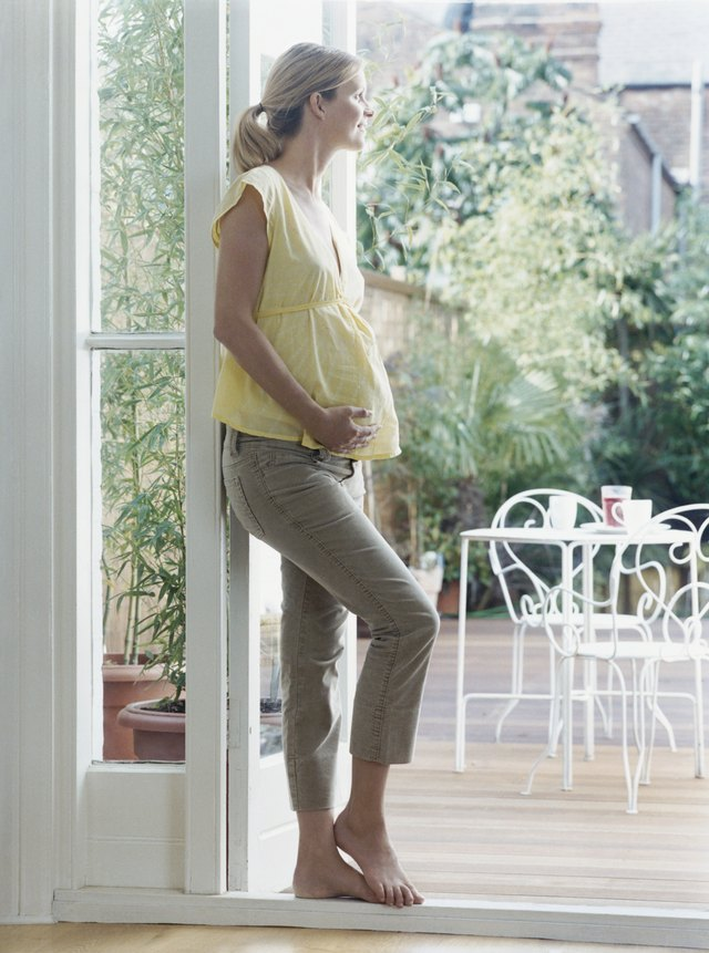 Pregnant Woman Leans Against a Door Looking at Garden