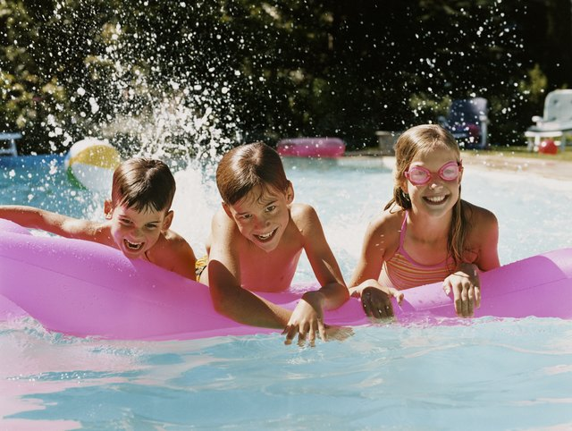 Three children in a Swimming Pool Playing With an Air Bed