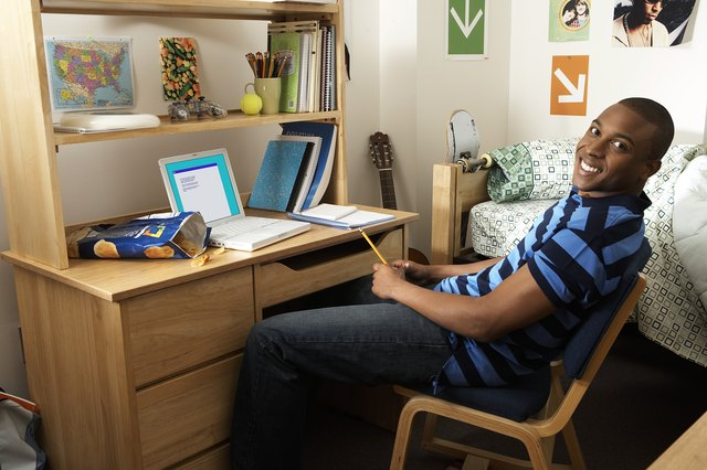 Young man sitting at desk in bedroom, smiling, portrait