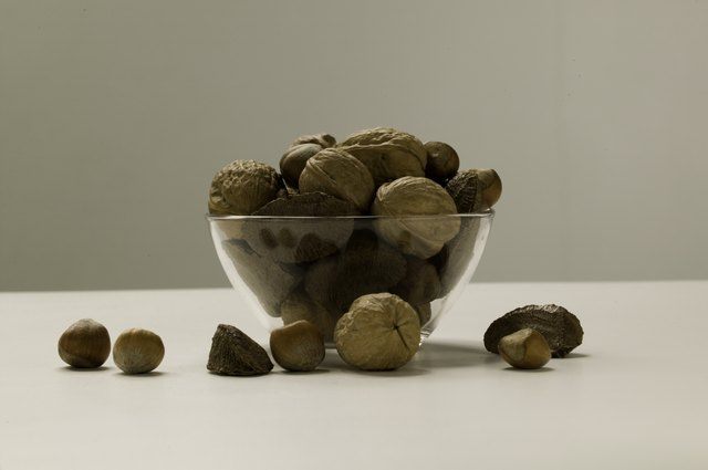 Assortment of nuts lying in glass bowl and around, studio shot, close-up