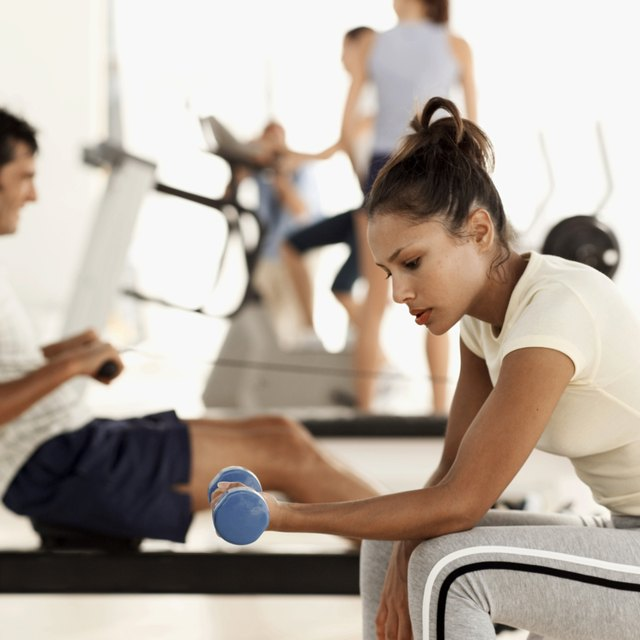 side view of a woman working out with a dumbbell at the gym
