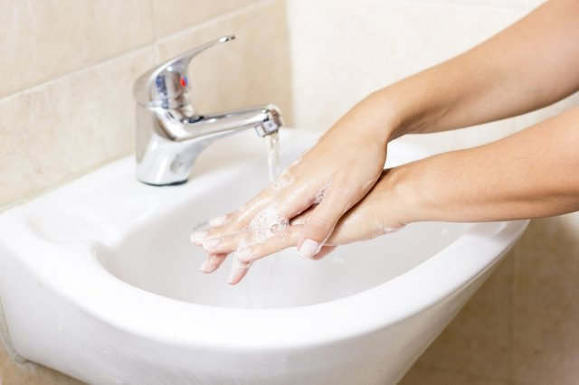 Woman washes with running water and soap hands