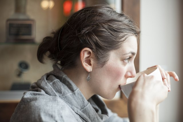 Beautiful Young Woman Drinking Her Morning Cup of Coffee