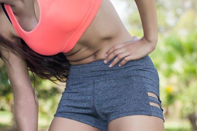 Woman in sport bra having a hip pain / Rheumatoid