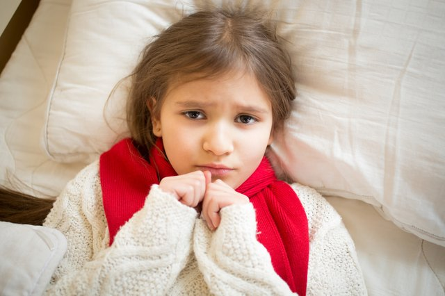 portrait of little sad girl with flu lying in bed