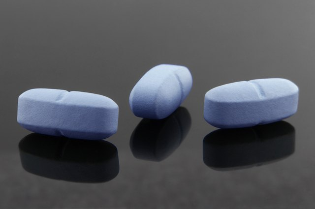 Blue pills and your reflections on dark background.