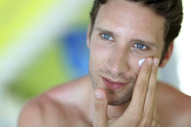 Portrait of man applying cream on his face