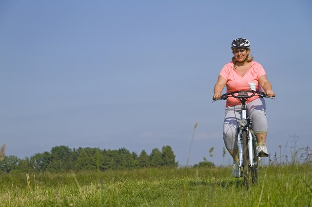 Mature woman cycling through field