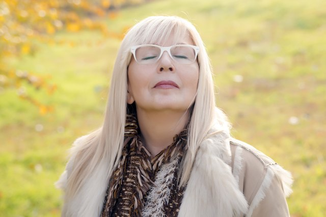 Portrait of a relaxed autumn mature woman breathing deep
