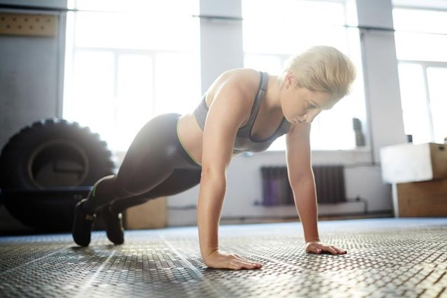 Young woman in sportive outfit doing press ups